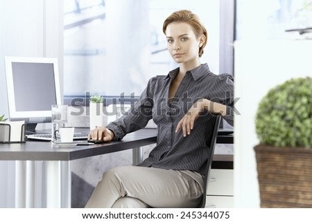 Attractive young businesswoman sitting at desk in office. - stock photo