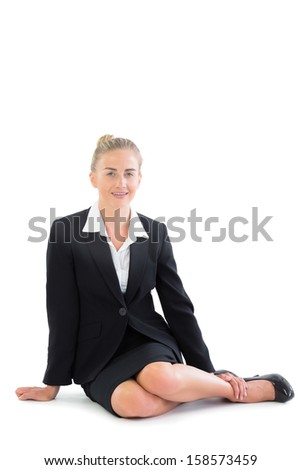 Attractive young businesswoman sitting on floor smiling at camera