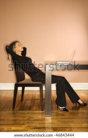 Attractive young businesswoman slouching in chair and looking up. A laptop is on the table in front of her. Vertical shot. - stock photo