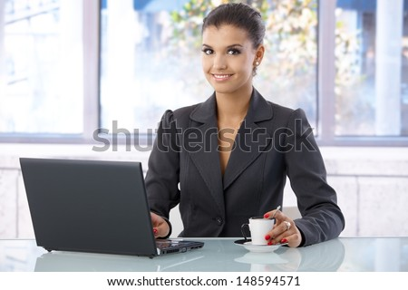 Attractive young businesswoman smiling in bright office, using laptop computer. - stock photo
