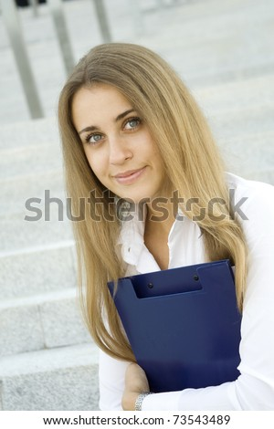 Attractive young businesswoman smiling with a folder