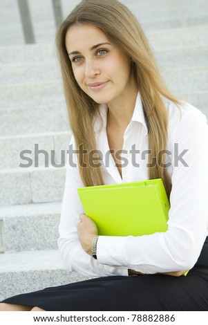 Attractive young businesswoman smiling with a green folder on the chest. - stock photo