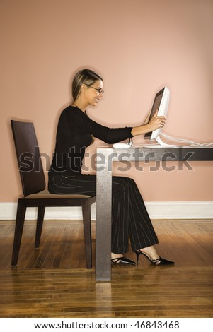 Attractive young businesswoman smiling with her hands on her computer. Vertical shot. - stock photo