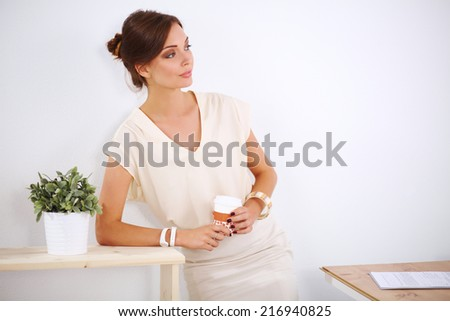 Attractive young businesswoman standing near desk in the office - stock photo