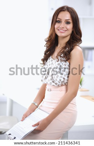 Attractive young businesswoman standing near desk with folder i - stock photo