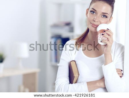Attractive young businesswoman standing  near wall in office - stock photo