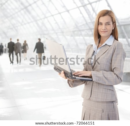 Attractive young businesswoman using laptop at office lobby, smiling.? - stock photo