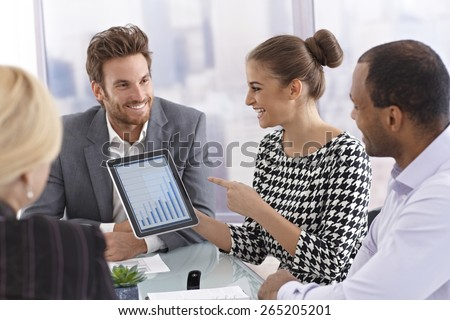Attractive young businesswoman using tablet to present business diagram at a meeting. - stock photo