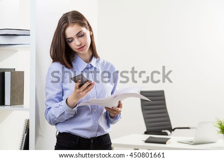 Attractive young businesswoman with documents in hand using mobile phone in modern office with bookshelves and workplace - stock photo
