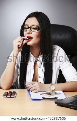 Attractive young businesswoman with long brunette hair sitting at her desk enjoying a chocolate - stock photo