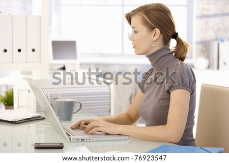 Attractive young businesswoman working at desk, using laptop computer, looking at screen. Side view.? - stock photo