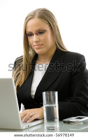 Attractive young businesswoman working on laptop computer at desk, isolated on white background. - stock photo