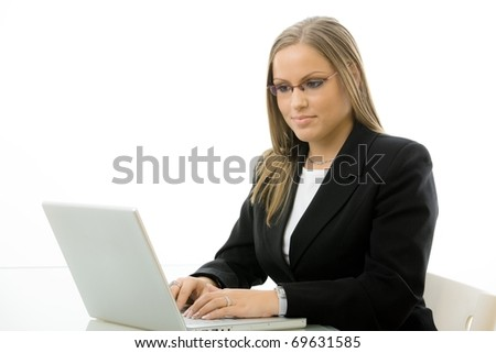 Attractive young businesswoman working on laptop computer at desk, isolated on white background.?