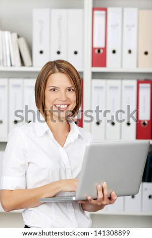 Attractive young businesswoman working on laptop, smiling, standing in office - stock photo