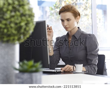 Attractive young businesswoman working with computer, sitting at desk, concentrating. Green plants in foreground. - stock photo