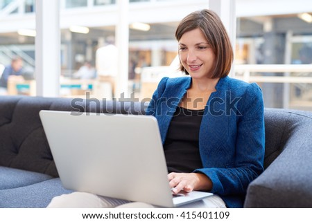 Attractive young busineswoman with laptop on couch in office - stock photo