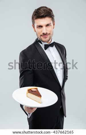 Attractive young butler in tuxedo standing and holding piece of cake on plate - stock photo