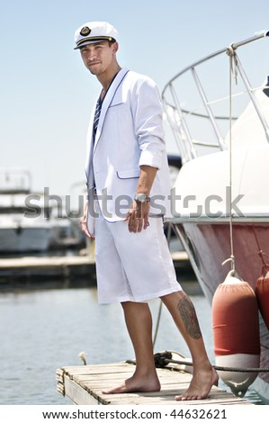Attractive young captain over the jetty beside his boat - stock photo
