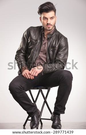 Attractive young casual man looking away from the camera while sitting on a chair. - stock photo