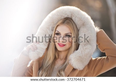 Attractive young Caucasian adult with light brown fur coat hood. Beautiful blonde girl with gorgeous eyes wearing fur, outdoor shot. Makeup - sensual long fair hair female art portrait, winter season - stock photo