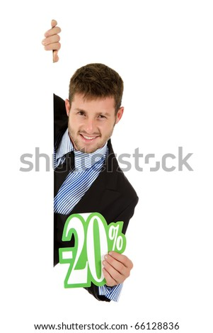 Attractive young caucasian businessman behind a wall showing twenty percent discount sign. Copy space. Studio shot. White background. - stock photo