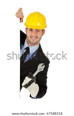 Attractive young caucasian businessman behind wall equipped with protective glove and helmet  holding a plumber spanner. Copy space. Studio shot. White background. - stock photo
