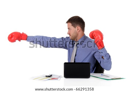 Attractive young caucasian businessman in office, wearing boxing gloves. Blow with right arm. Studio shot. White background. - stock photo