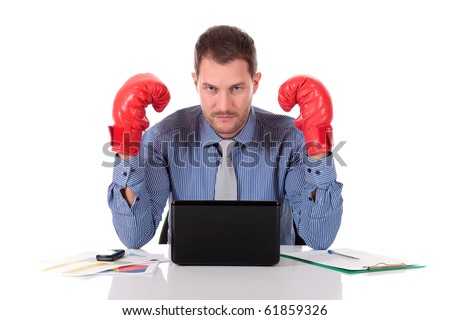 Attractive young caucasian businessman in office, wearing boxing gloves looking angry. Studio shot. White background. - stock photo