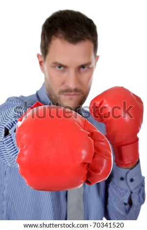 Attractive young caucasian businessman wearing boxing gloves. Focus on glove. Blow with right arm. Studio shot. White background. - stock photo