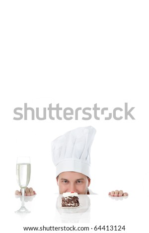 Attractive young caucasian chef man being tempted, peeping above table. Studio shot. White background. Copy space. focus on eyes. - stock photo