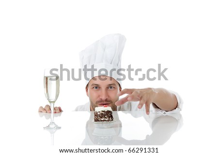Attractive young caucasian chef man being tempted, ready to take the pastry from table. Studio shot. White background. - stock photo