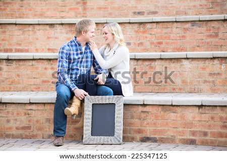 Attractive young caucasian couple in love, sitting on steps while smiling at each other - stock photo