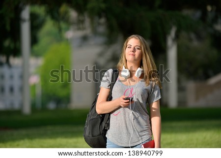 Attractive young Caucasian female student walking on campus with headphones around her neck, carrying backpack.
