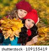 attractive young caucasian woman and girl in warm colorful clothing  lying on yellow leaves outdoors smiling - stock photo