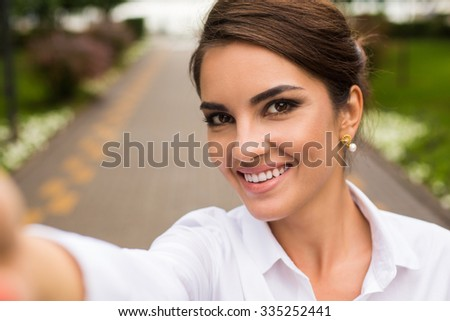 Attractive young caucasian woman doing selfie - stock photo