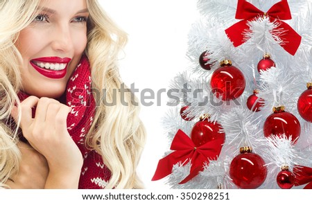 attractive young caucasian woman in warm clothing  in studio isolated on white smiling hat warm christmas tree red balls