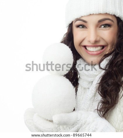 attractive young caucasian woman in warm clothing outdoors smiling with snowball