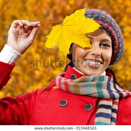 attractive young caucasian woman in warm colorful clothing  on yeloow leaves outdoors smiling - stock photo
