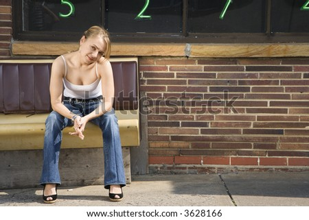 Attractive young Caucasian woman sitting on bench outside. - stock photo
