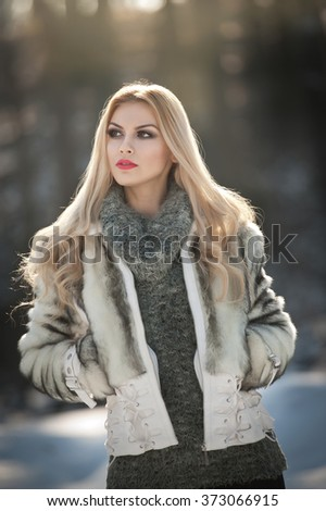 Attractive young Caucasian woman with short fur jacket in winter park. Beautiful blonde girl with gorgeous eyes and long hair, outdoor shot in bright cold day, makeup - sensual female art portrait