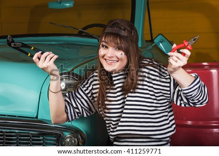 attractive young cheerful woman in a baseball cap sits in the garage near the retro car with tools. Girl holding pliers and an adjustable wrench and smiling - stock photo