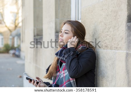 Attractive young city girl listening to music on her mobile phone leaning against a commercial building as she selects a new tune from her library, with copy space