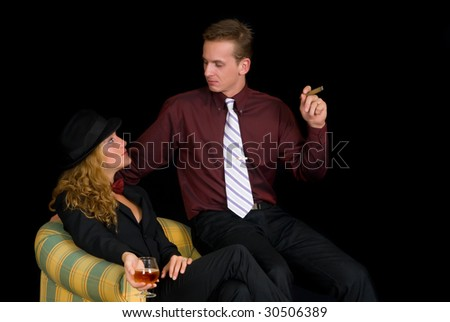 Attractive young classy couple, formal clothing, woman wearing suit and bow tie.  Studio shot, black background.