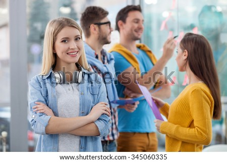 Attractive young colleagues are discussing new project. They are standing and smiling. The woman is looking at camera confidently. The man is writing on sticker - stock photo