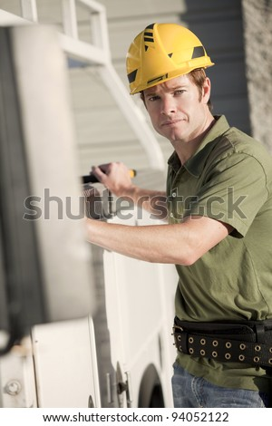 Attractive young construction worker with hardhat - stock photo