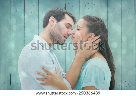 Attractive young couple about to kiss against blue abstract light spot design - stock photo