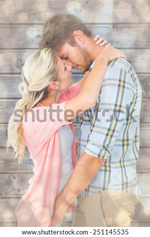 Attractive young couple about to kiss against light glowing dots design pattern - stock photo