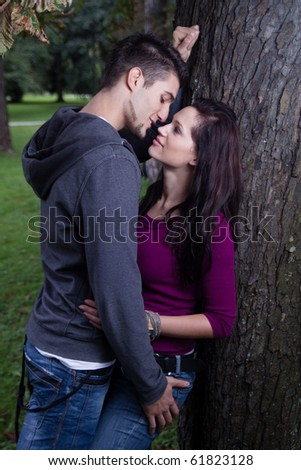 Attractive young couple about to kiss under a tree in a park. - stock photo