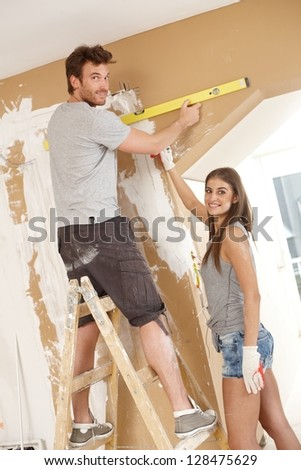 Attractive young couple building new home using spirit level to measure. - stock photo