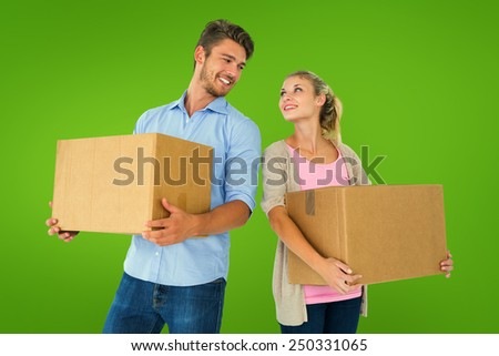 Attractive young couple carrying moving boxes against green vignette - stock photo